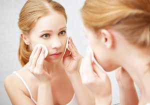 beautiful young woman removes makeup with face skin cotton pad in the mirror